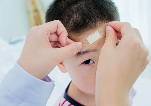 Young boy getting bandage placed on forehead